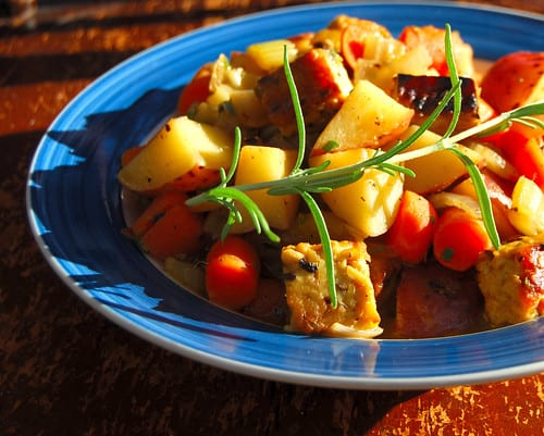 Vegan Herbed Tempeh Stew in a blue and white bowl with sprigs of rosemary.