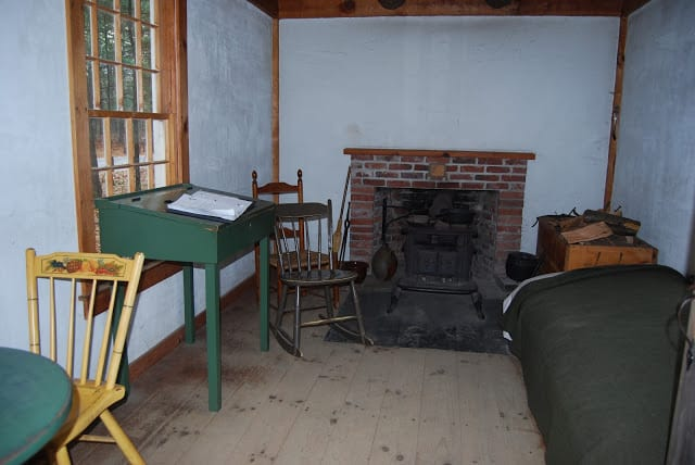 View inside Thoreau's cabin at Walden with a fireplace, three chairs, a writing table, a bed and firewood.