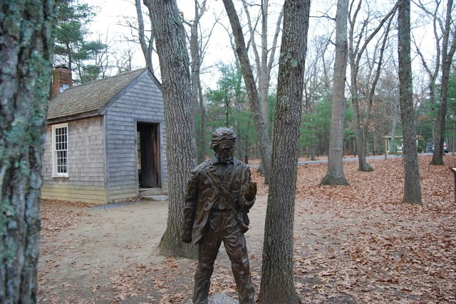Outside view of Thoreau's cabin in Walden with a statue of Thoreau outside.