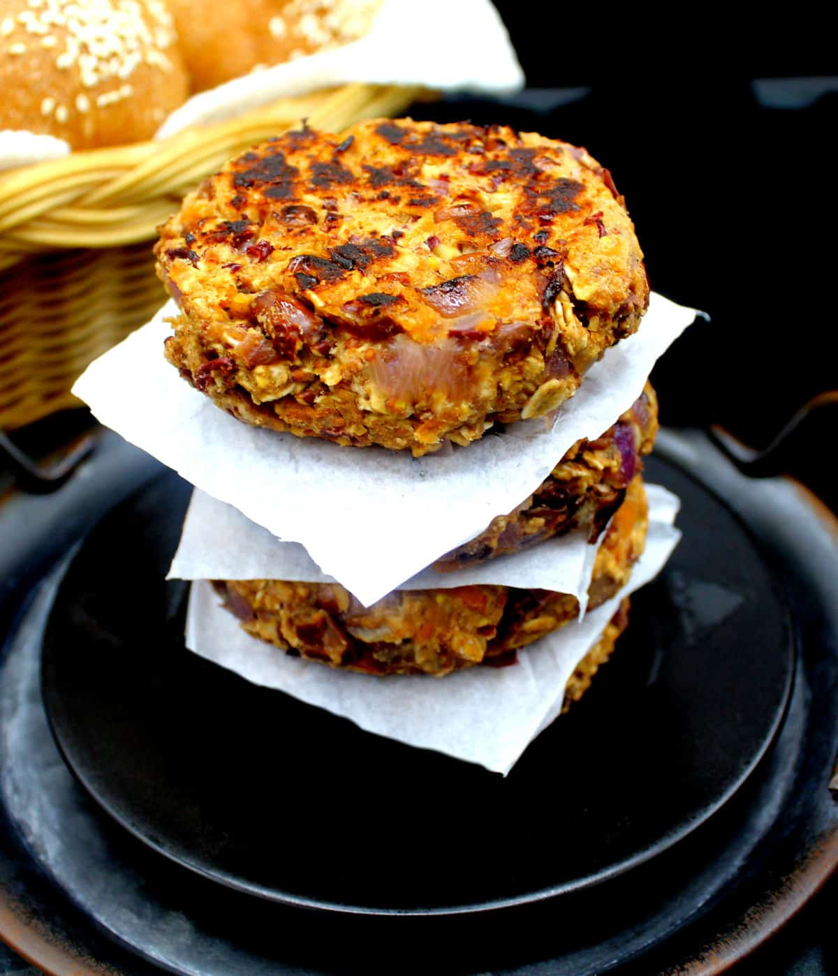 Photo of four bean and oats burger patties separated with parchment stacked on a black plate.