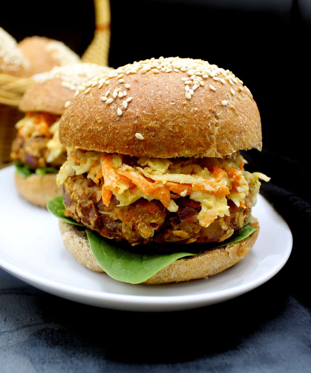 Front shot of a vegan bean and oats veggie burger with greens, coleslaw and served in a whole wheat burger bun on a white plate.