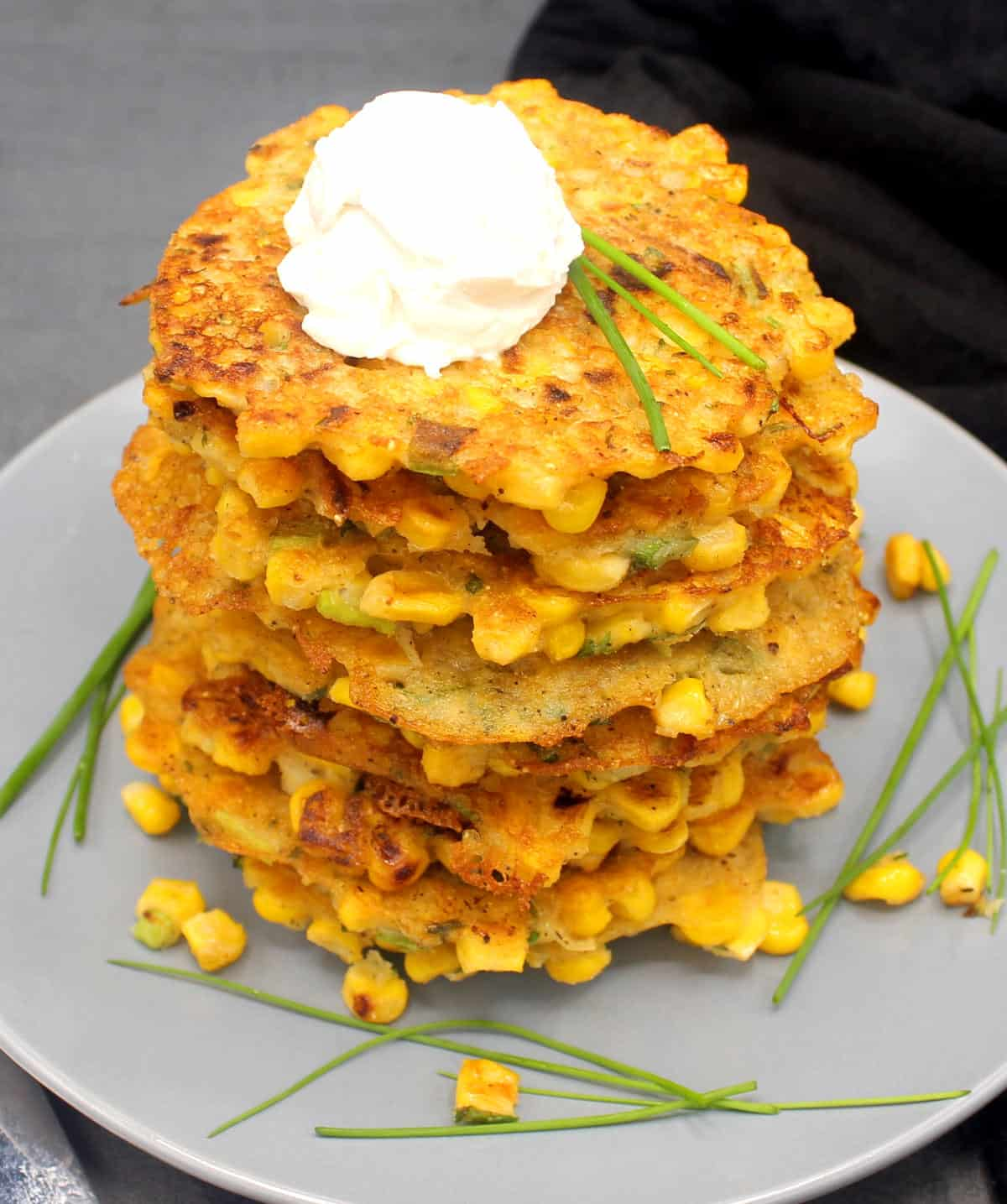 Photo of a stack of vegan corn fritters on a gray plate with vegan cream cheese and chives
