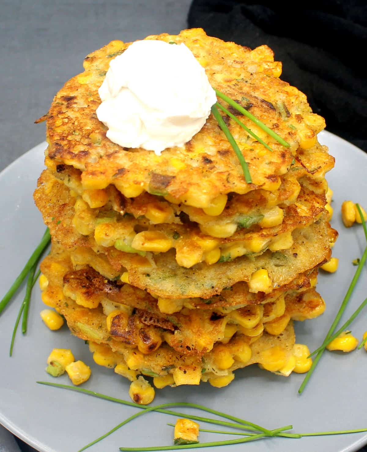 A stack of vegan corn fritters on a gray plate with vegan cream cheese and chives