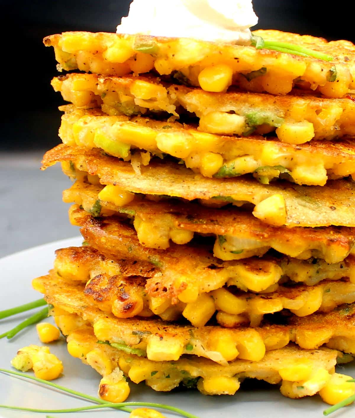Closeup photo of a stack of vegan corn fritters on a gray plate with vegan cream cheese and chives