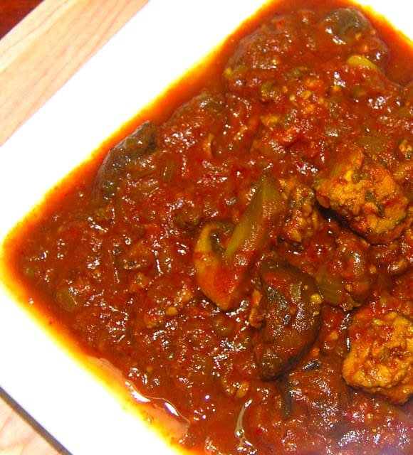 Photo of vegan doro wat, an Ethiopian stew, in a square white plate.