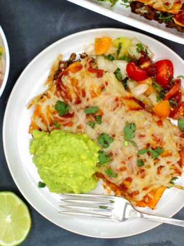 Vegan enchiladas served with a fresh tomato salsa, guacamole on a white plate with a fork.