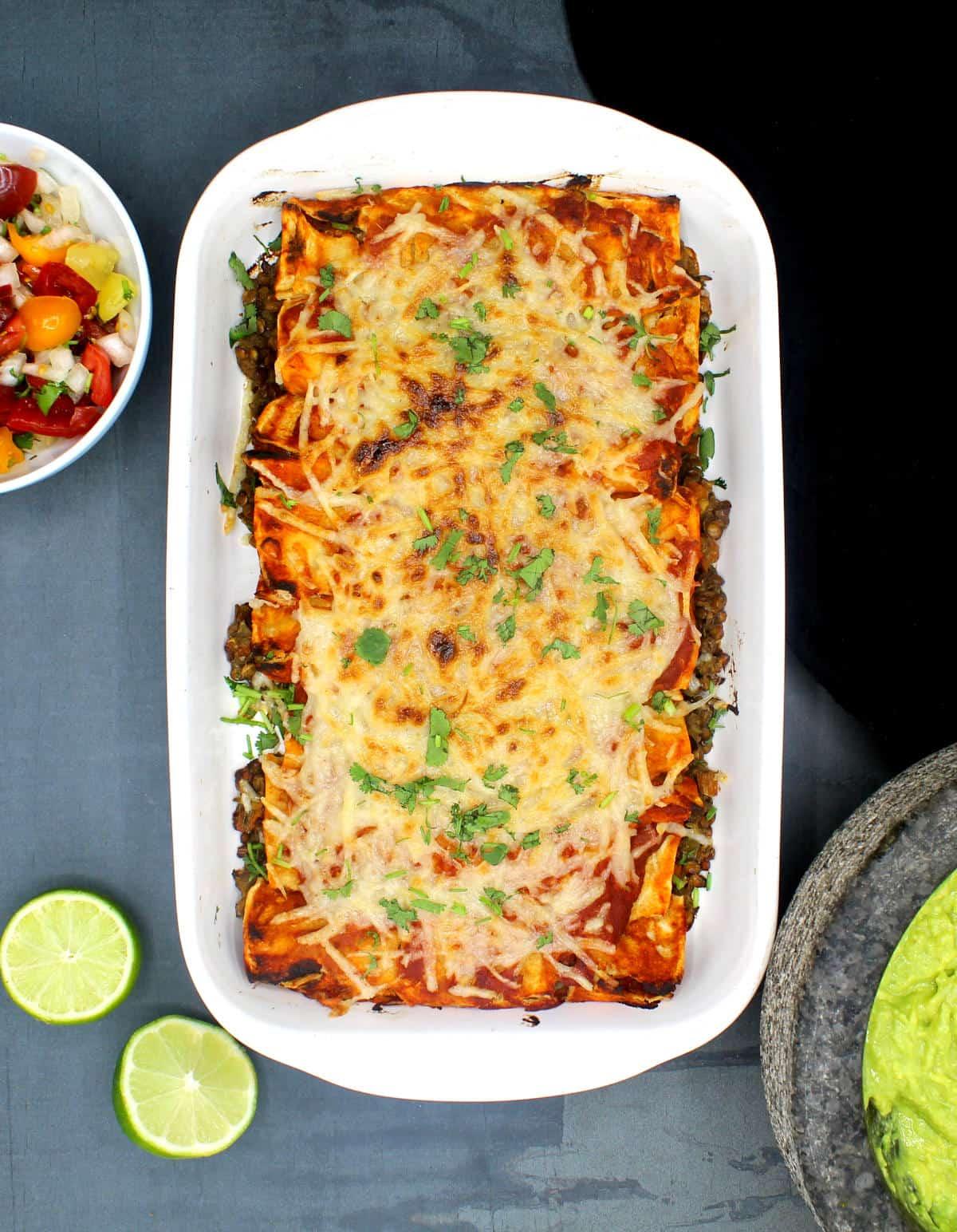 The vegan enchilada casserole with tomato and onion salsa, guacamole in molcajete and limes.