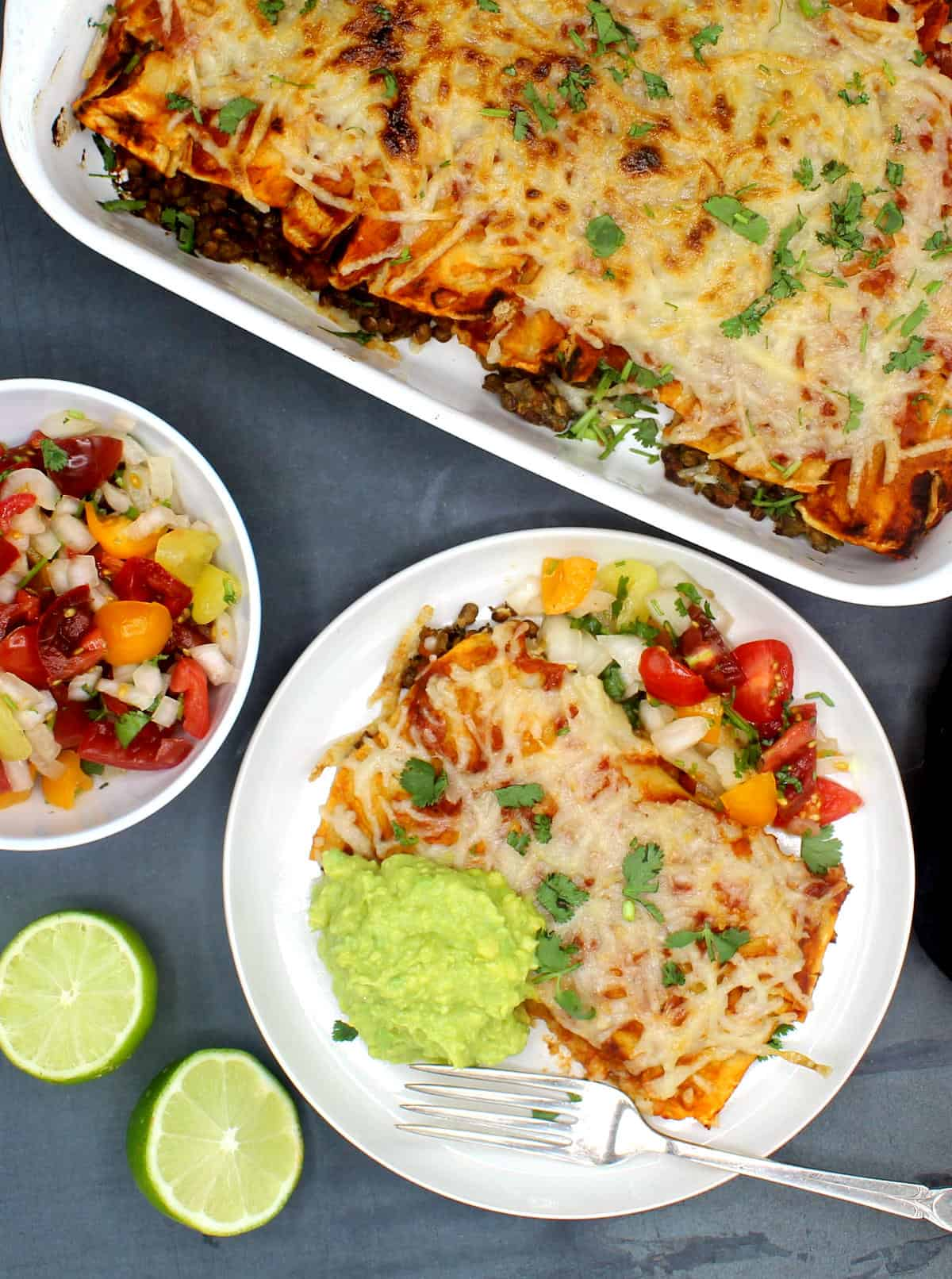 Vegan enchiladas served with a fresh tomato salsa, guacamole on a white plate with a fork. Whole enchilada casserole and limes in background.