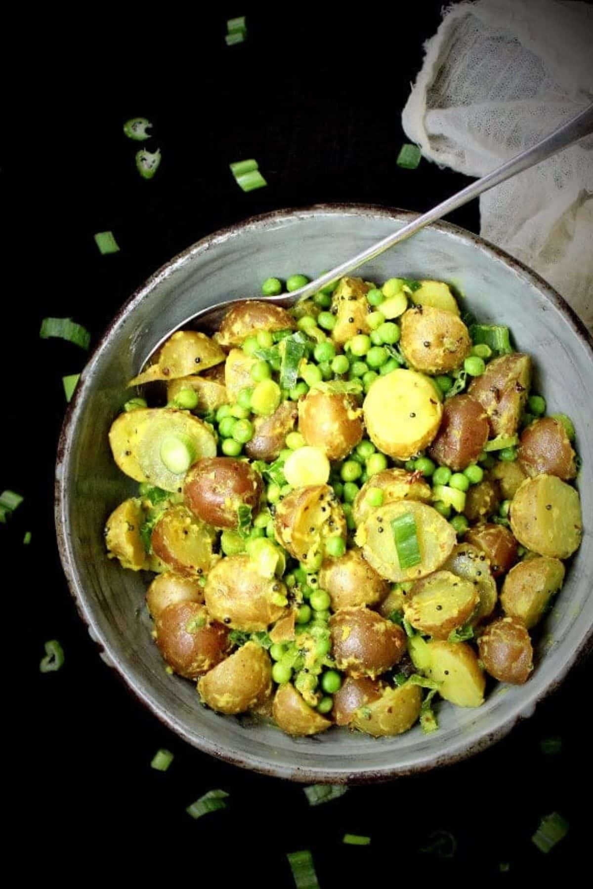 Overhead photo of creamy vegan potato salad made with Indian flavorings like coconut, ginger and turmeric in a glazed green and brown bowl with cheesecloth next to it.