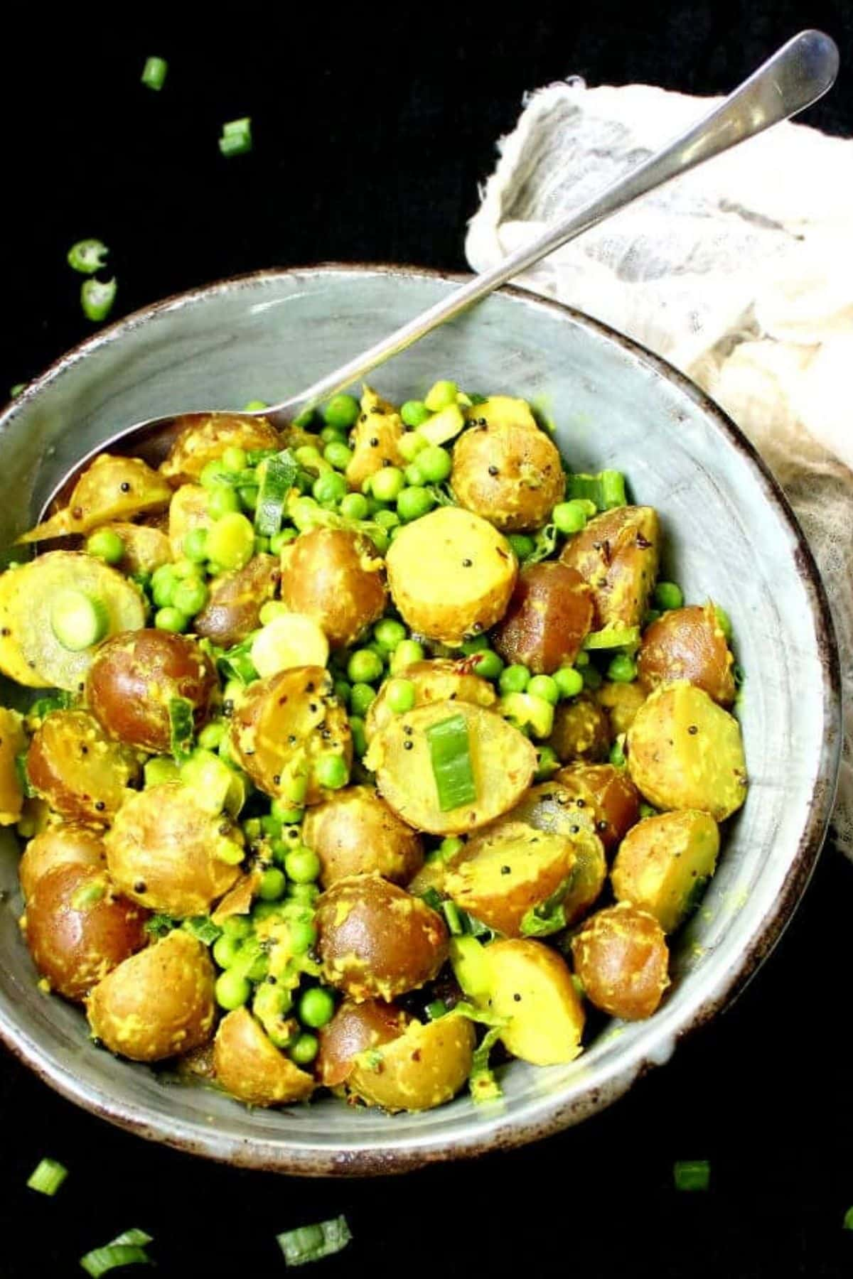 Photo of vegan potato salad made with Indian flavorings like coconut, ginger and turmeric in a glazed green and brown bowl.