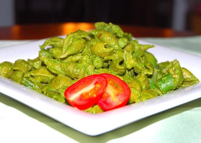 Photo of a plate of conchiglie or shell pasta with a green, fresh, vegan kale pesto and a slice of tomato.