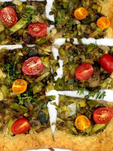 Closeup of vegan leek scallion pizza with cherry tomatoes, capers and fresh sprigs of thyme