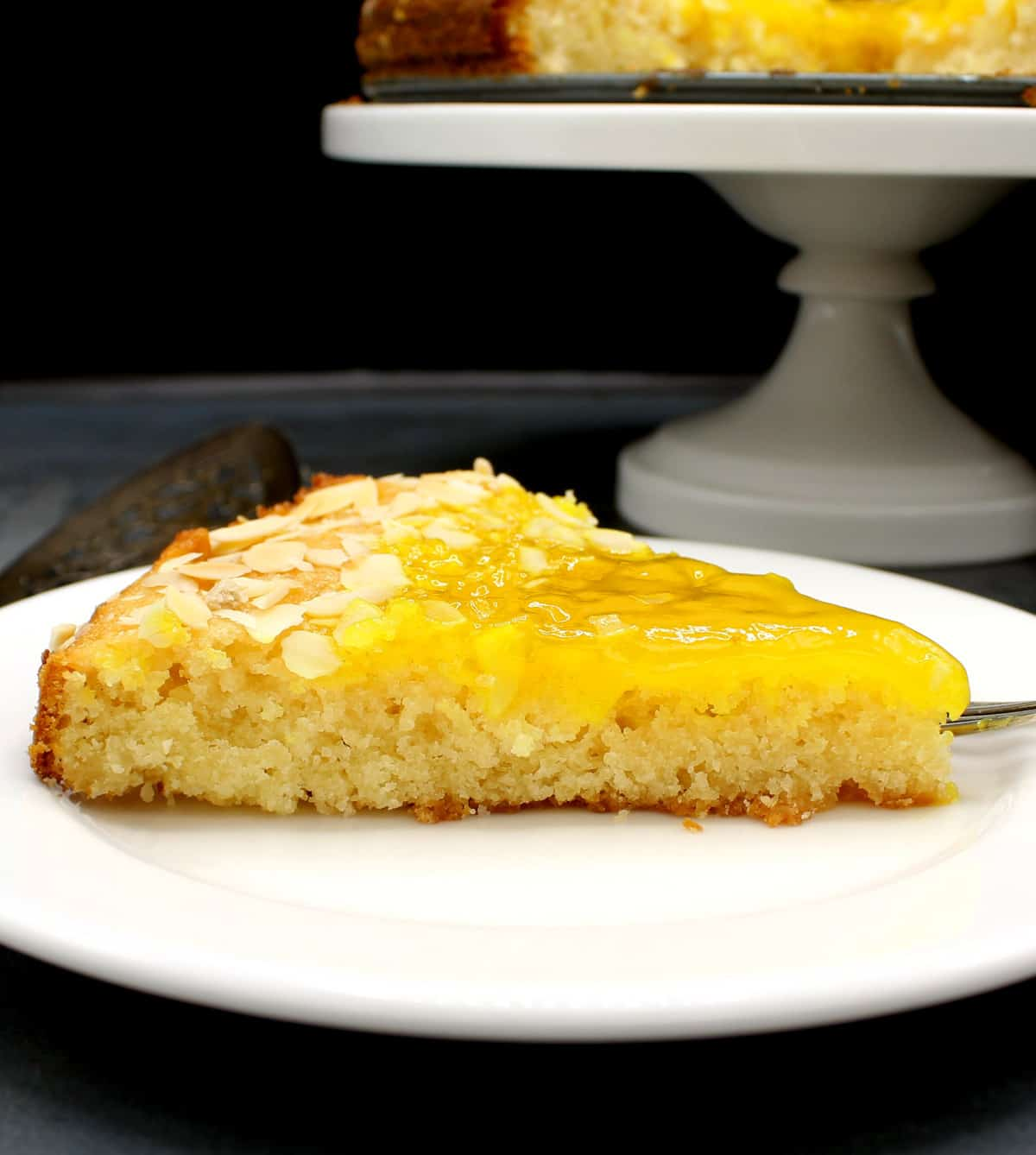 Photo of a slice of vegan lemon cake with lemon curd topping on a white plate with the full cake in background.