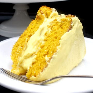A luscious slice of vegan mango cake with smooth, creamy mango buttercream frosting on a white plate with a fork.