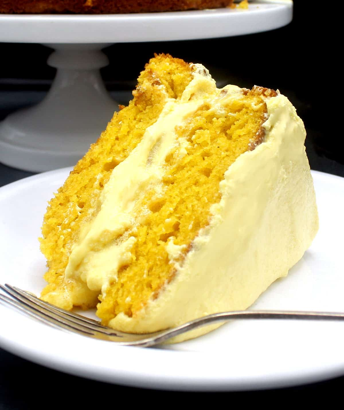Photo of a slice of vegan mango cake with a spongy, soft, orange crumb and fluffy mango buttercream on a white plate with a fork.