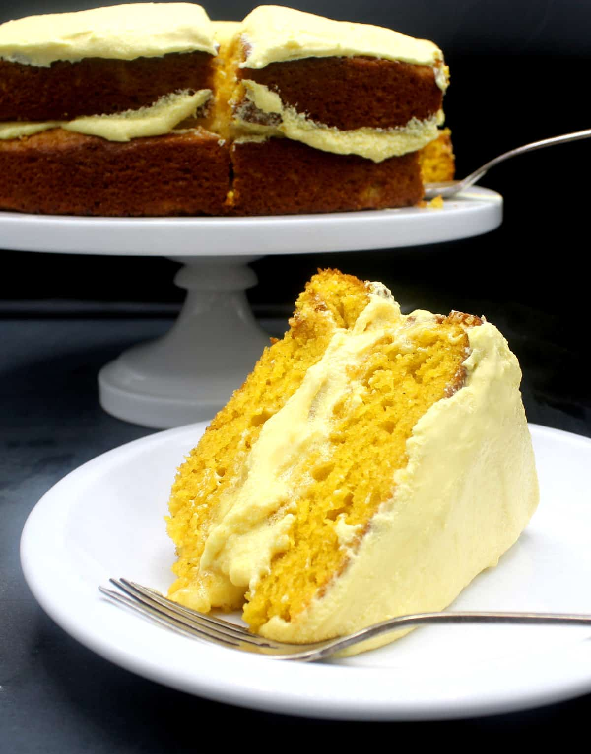 Photo of a slice of mango cake with mango buttercream on white plate with a fork and the sliced cake in the background.