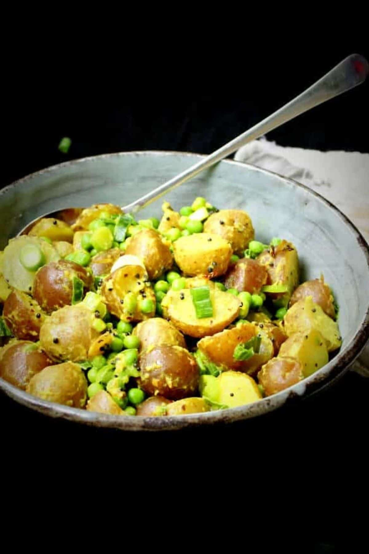 Front photo of vegan potato salad in a glazed green and brown bowl.