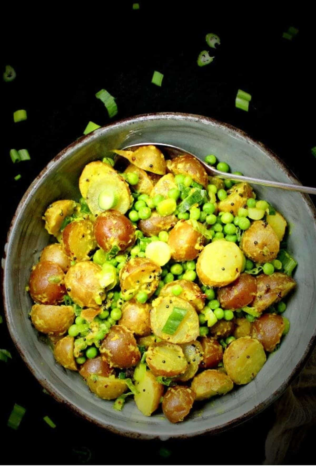 Overhead photo of vegan potato salad in a bowl on a black background.