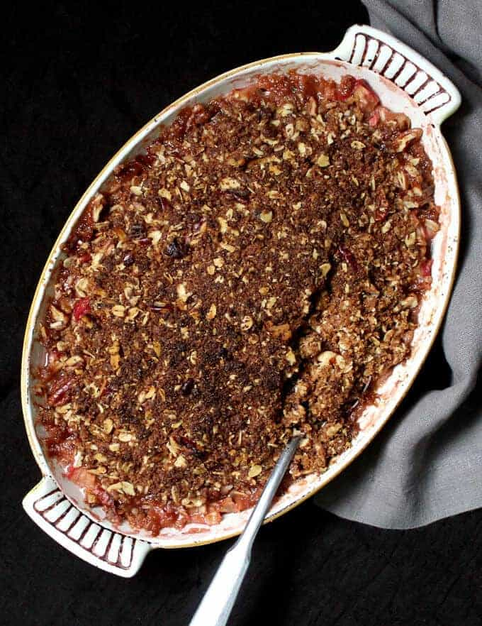 Overhead photo of a freshly baked, homemade vegan rhubarb crisp with oat and nut topping.
