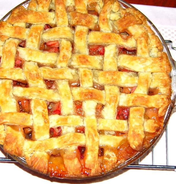 Photo of a lattice-top vegan rhubarb pie on a cooling rack.