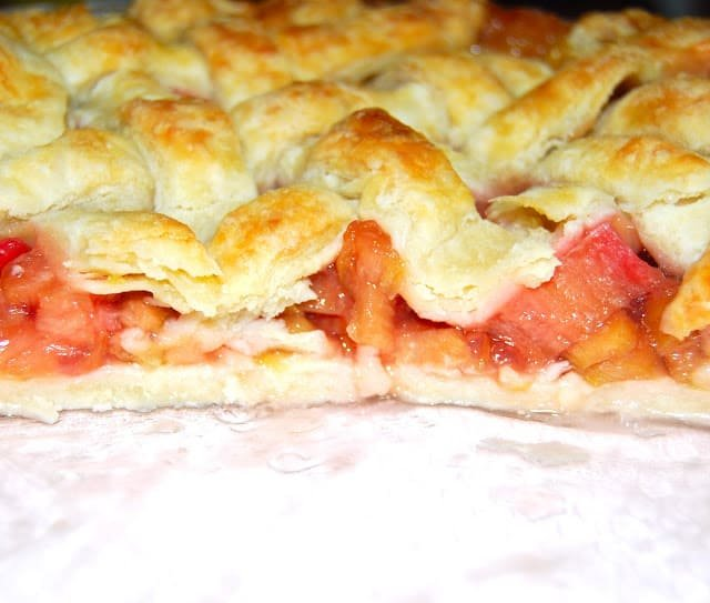 Photo of a cross section of a vegan rhubarb pie showing the sweet-tart, red rhubarb filling inside a golden pie pastry crust.