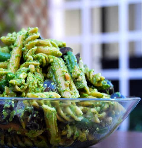 Pasta with vegan spinach pesto, green beans and olives in a glass bowl.