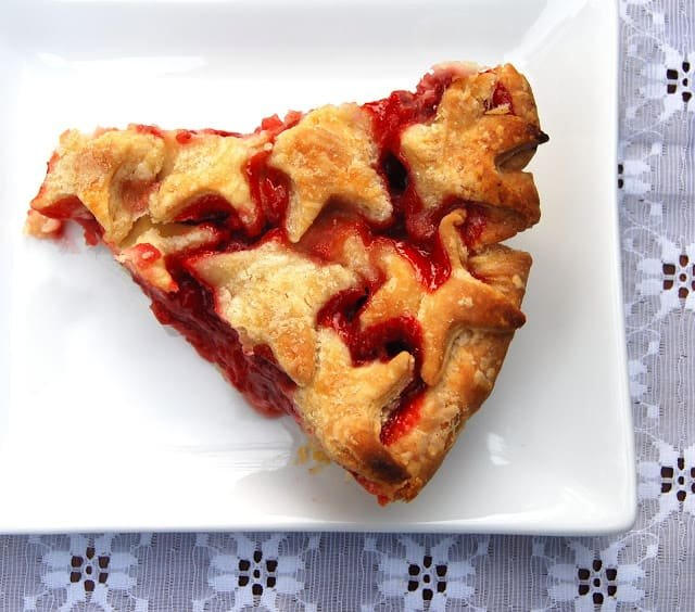 Photo of a vegan strawberry pie slice on a white plate on a lace tablecloth.