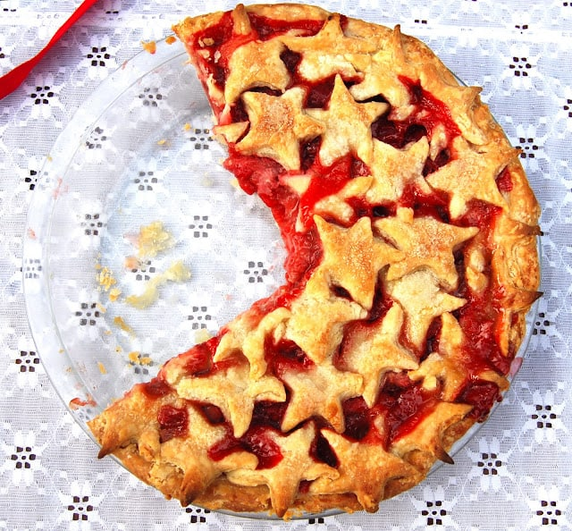 Photo of a vegan strawberry pie in a glass baking plate with a starry golden crust and on a lace tablecloth.