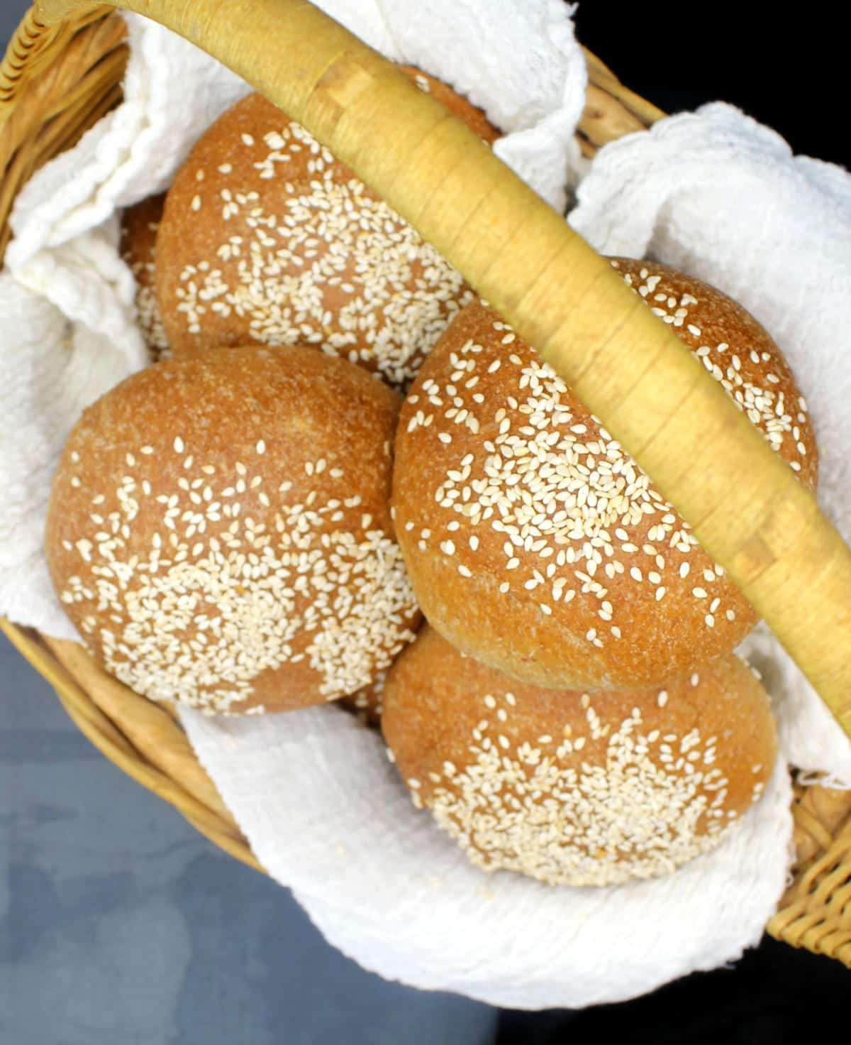 Overhead photo of whole wheat hamburger buns nestled in cheesecloth in basket.