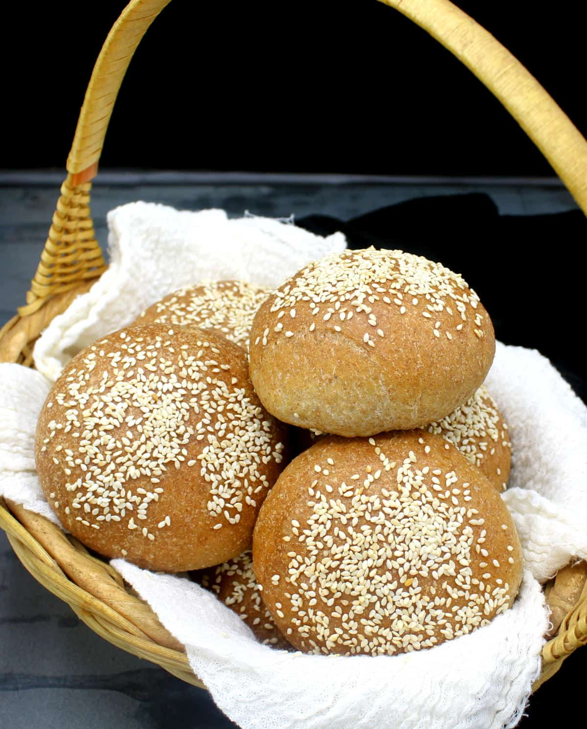 Photo of homemade vegan burger buns nestled in cheesecloth in a straw basket.