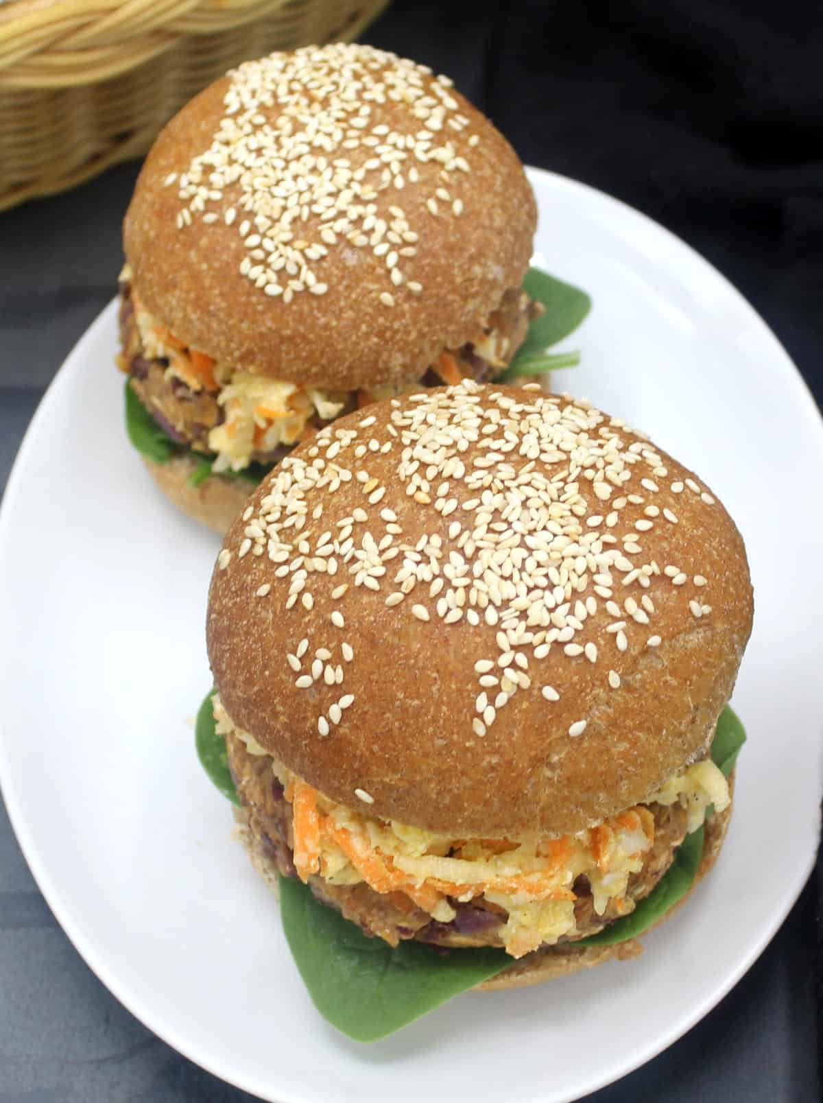 Photo of two bean and oats burgers in whole wheat buns with sesame seeds on a white plate.