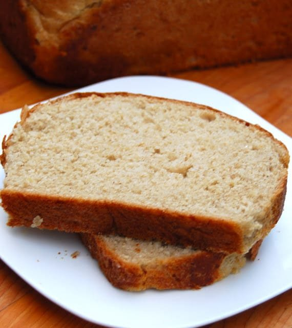 Two slices of whole wheat maple oatmeal bread on a white plate.