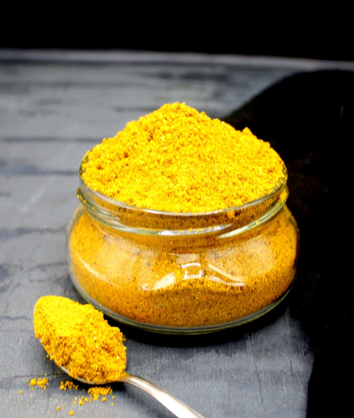 Photo of a glass jar of curry powder with a spoon next to it.