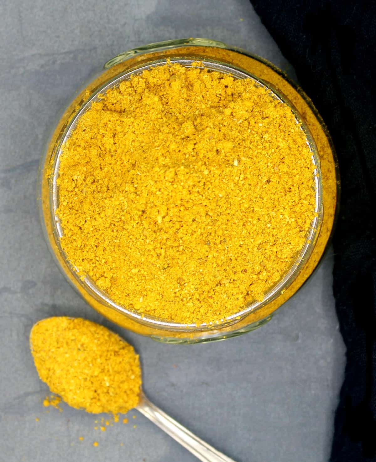 Overhead photo of a jar of yellow curry powder with a spoon.