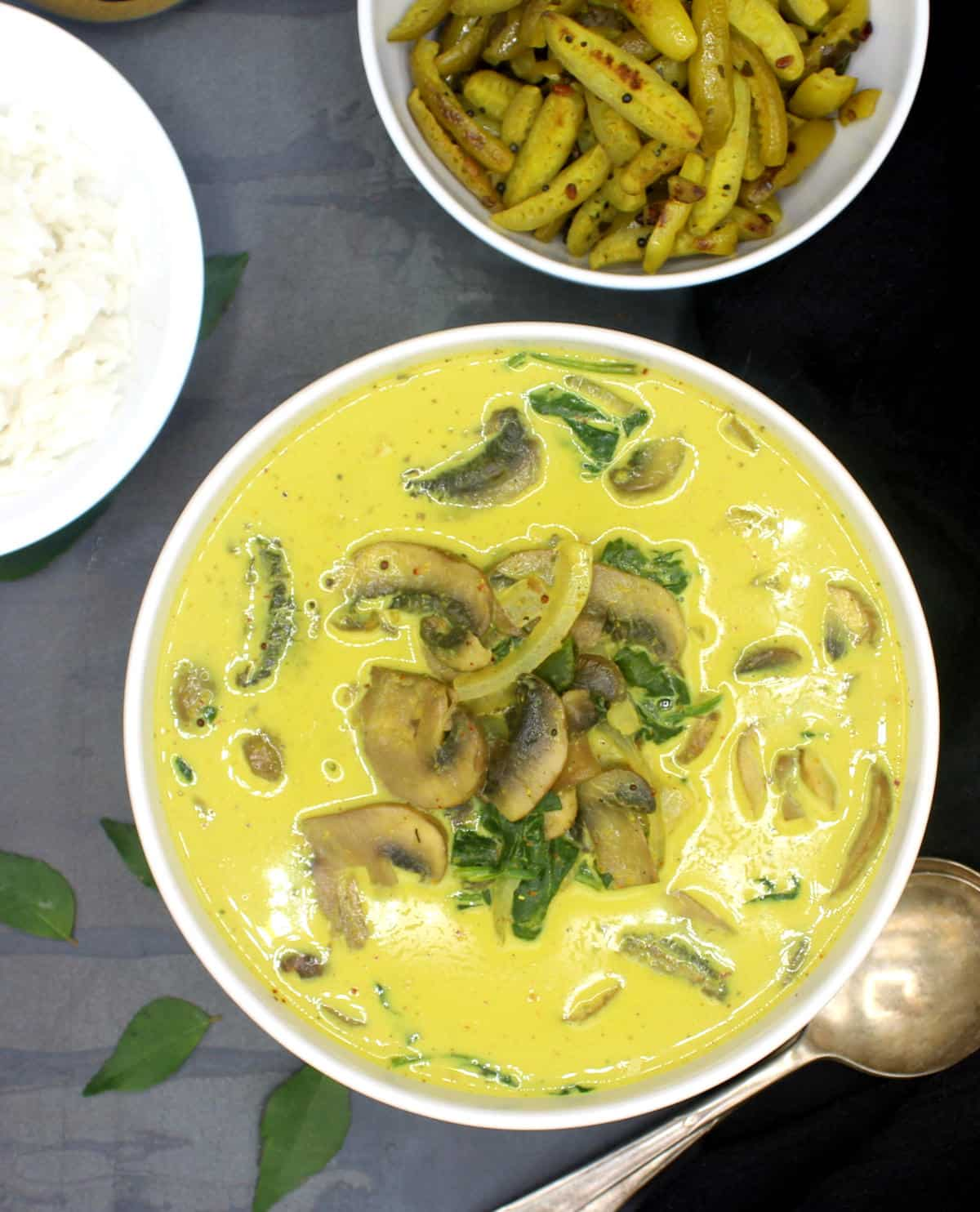 Photo of a curry made with curry powder and coconut milk in a white bowl with soup spoons and curry leaves.