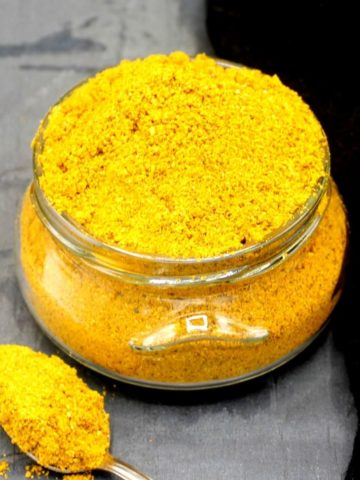 Photo of curry powder in a glass jar with a spoon next to it.