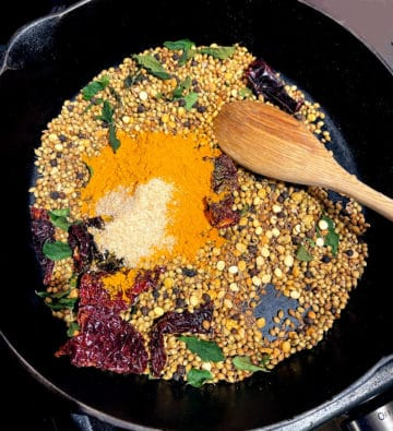 Turmeric and asafetida added to other roasted spices in skillet for curry powder