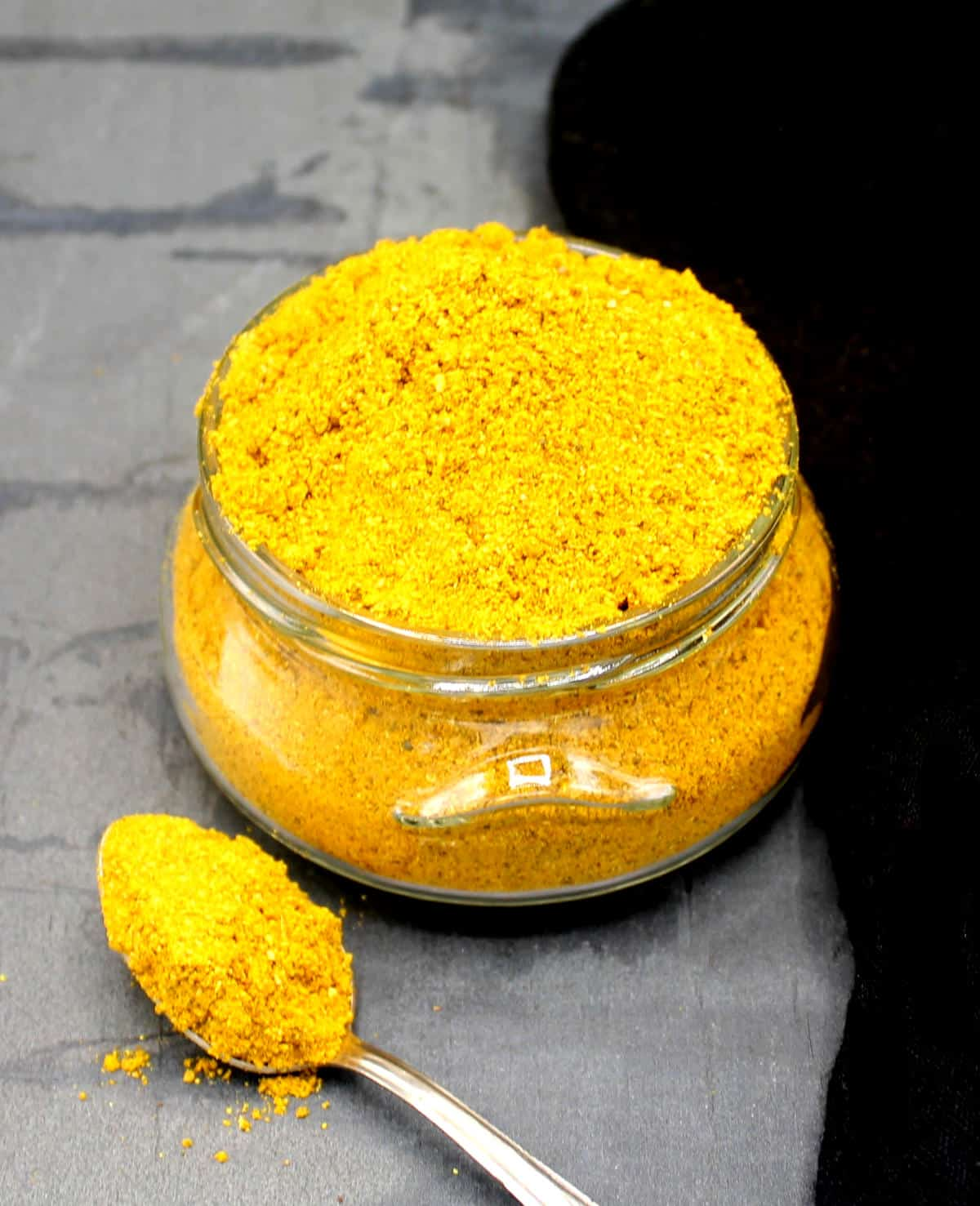 Photo of bright yellow curry powder in a glass jar with a spoon next to it.