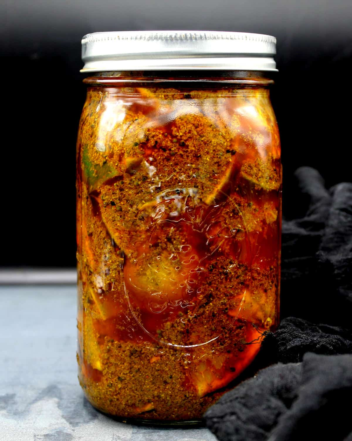 A mason jar with the lime pickle fermenting.