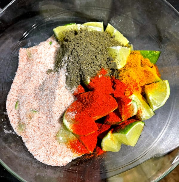 masala spices for lime pickle in bowl with quartered limes