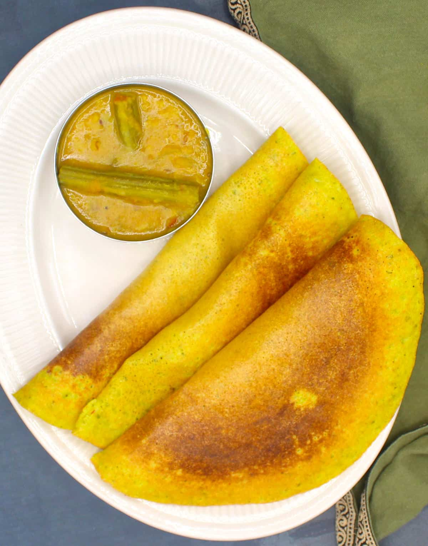 Three adai dosas on white plate with drumstick sambar.