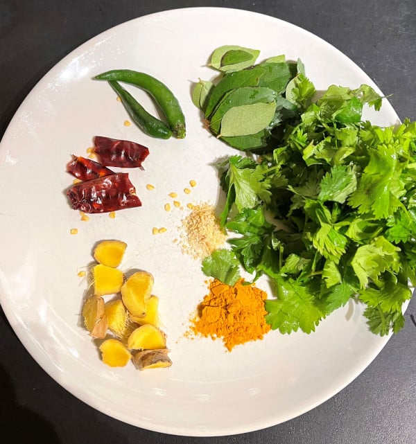 Masala ingredients for south Indian Adai including ginger, chili peppers, cilantro, curry leaves, asafetida and turmeric.