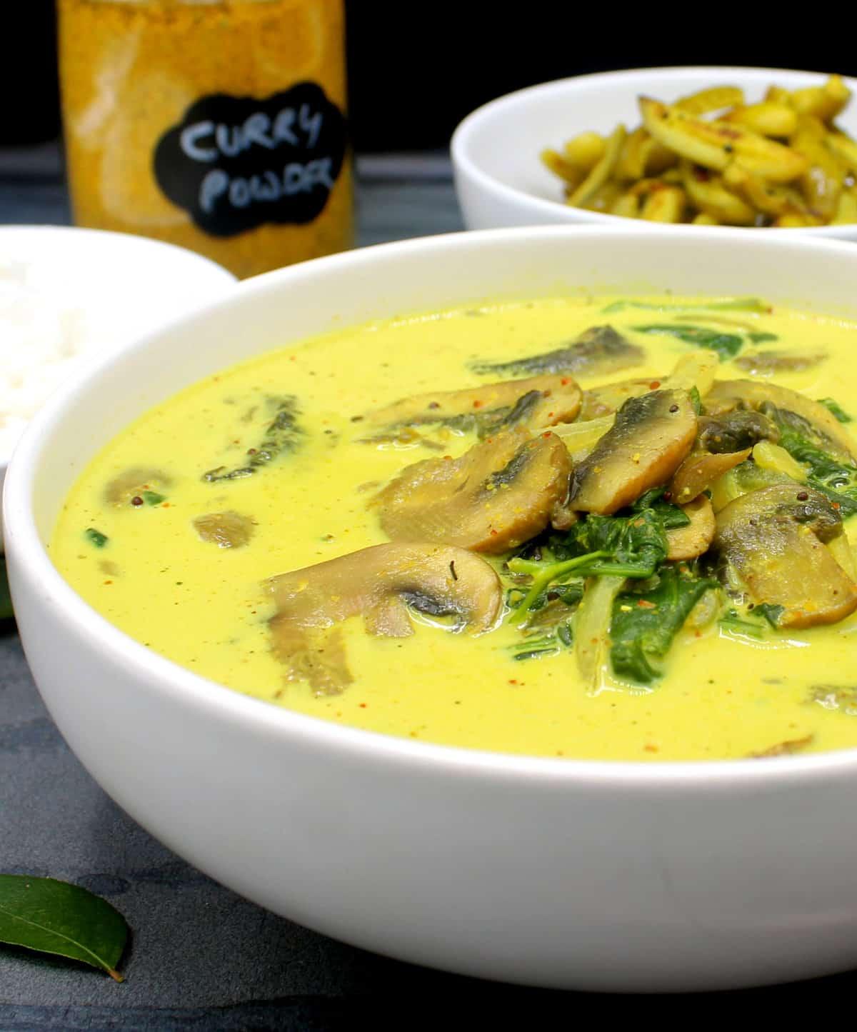 Closeup of a bowl of creamy vegan mushroom spinach curry.