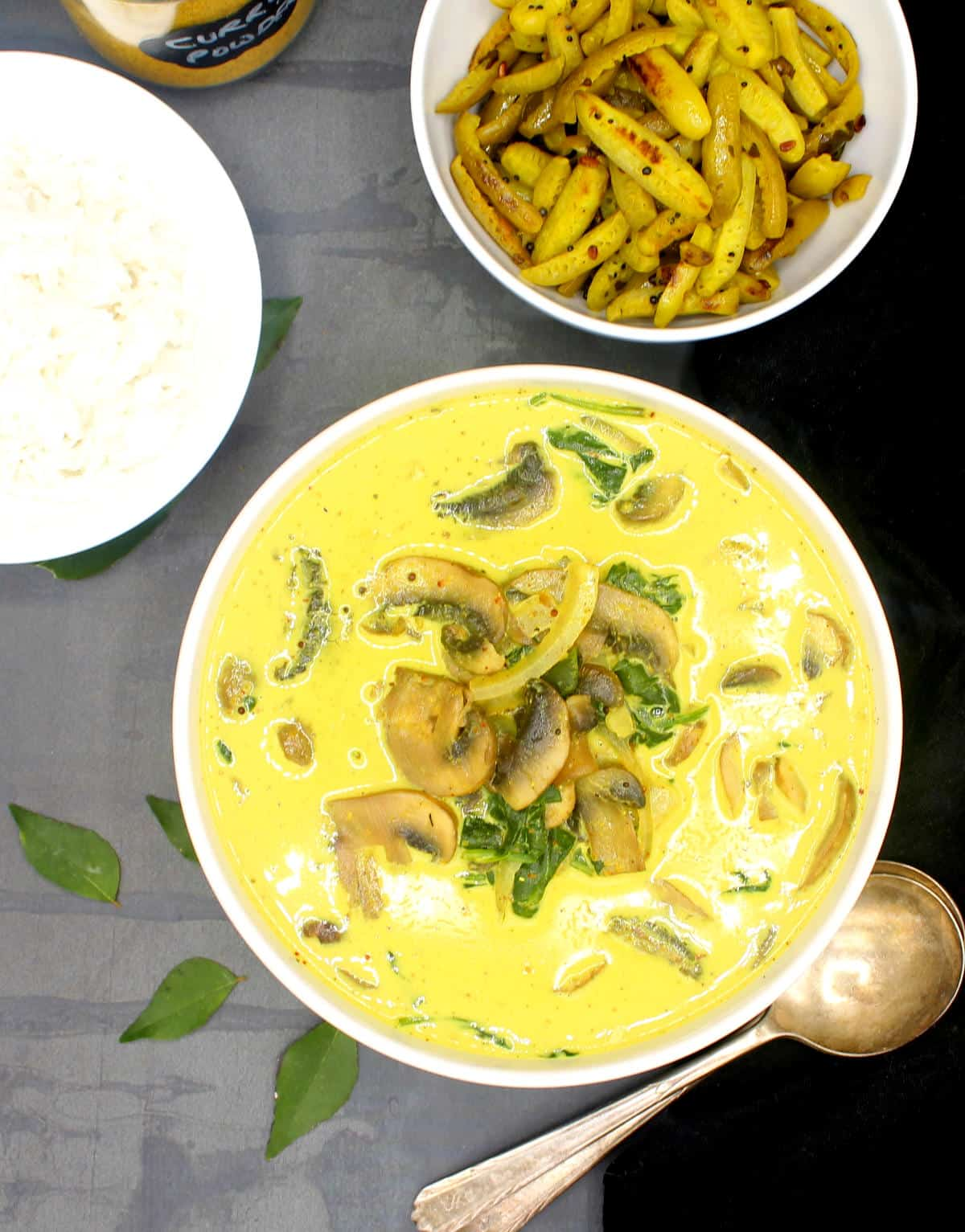 Photo of creamy mushroom spinach curry in a white bowl with rice and a vegetable side.