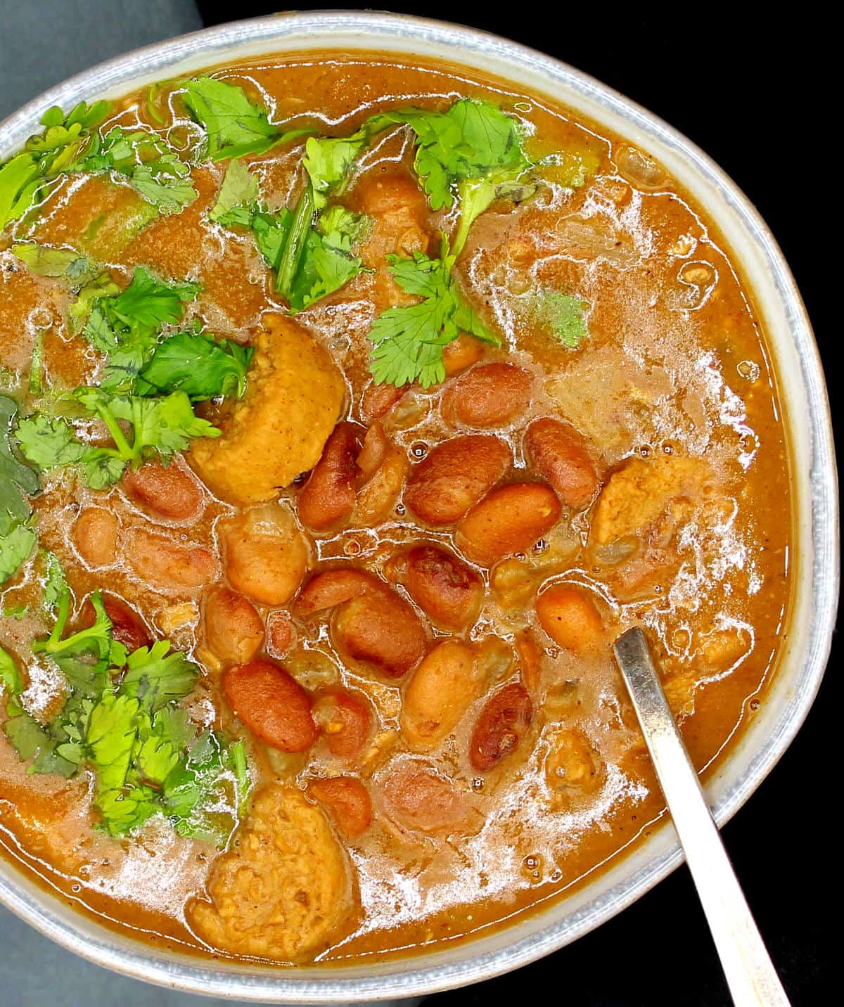 Photo of vegan Goan Feijoada in a ceramic bowl with sausages, pinto beans and cilantro.