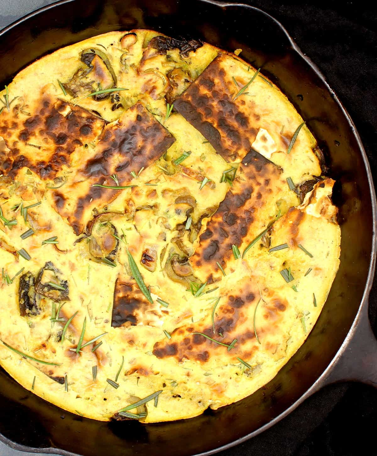 Photo of vegan matzo brei with chickpea eggs, mushrooms and shards of matzo crackers in a cast iron skillet.