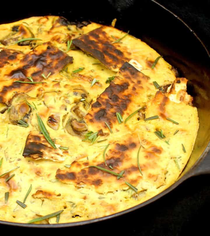 Closeup of a vegan matzo brei with charred matzo crackers in skillet.