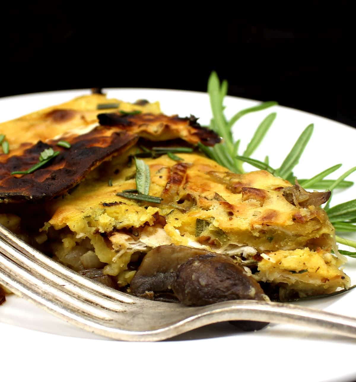 A closeup photo of a slice of vegan matzo frittata with rosemary and a fork.
