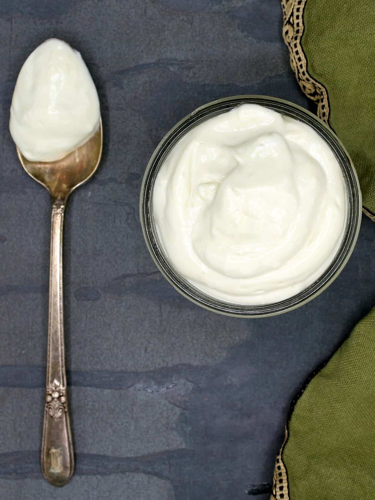 Overhead photo of creamy vegan mayo in glass jar with a silver spoon with mayo on the side and a green napkin.