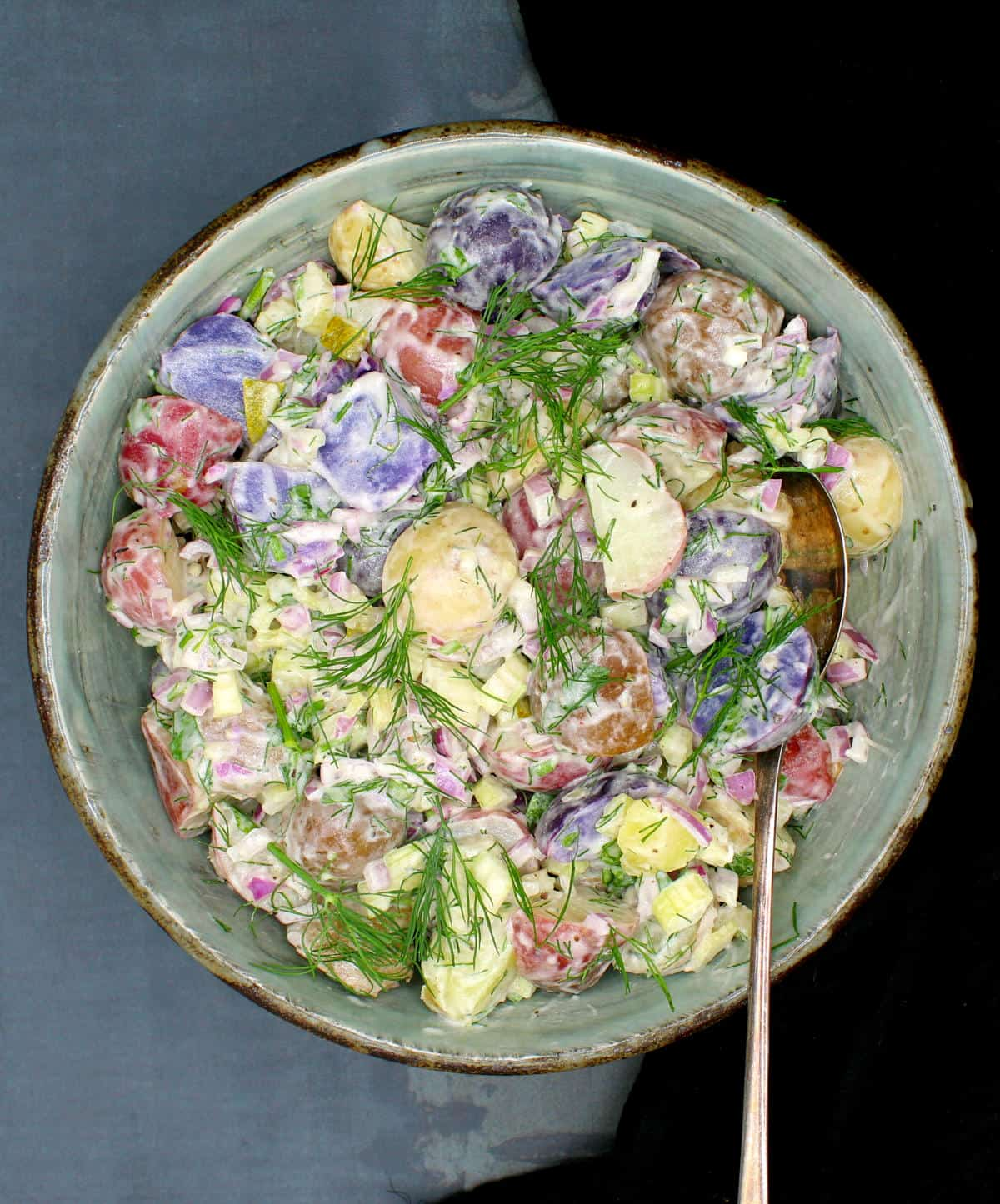 Overhead photo of vegan potato salad in a glazed clay bowl with creamy mayo, pickles, mustard, shallots, celery and wisps of dill.